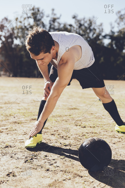 Man touching toes to stretch in soccer field