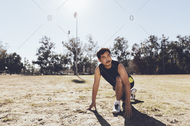 Man kneeling to stretch in a soccer field