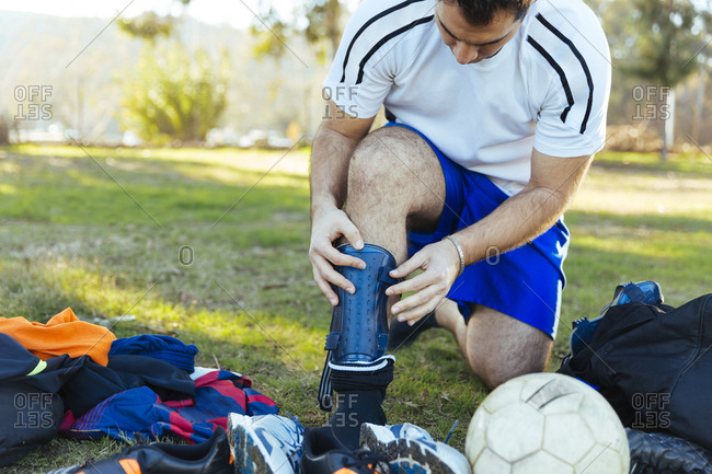Man putting on a shin guard for soccer