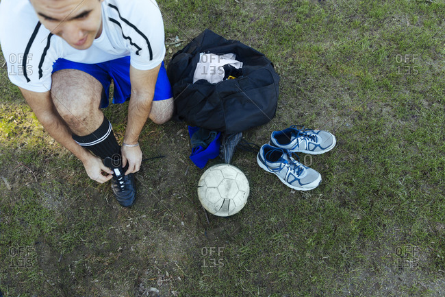 Man tying shoelaces to play soccer