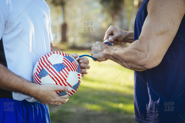 Two men pumping up soccer ball