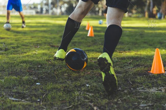 Man kicking soccer ball in training