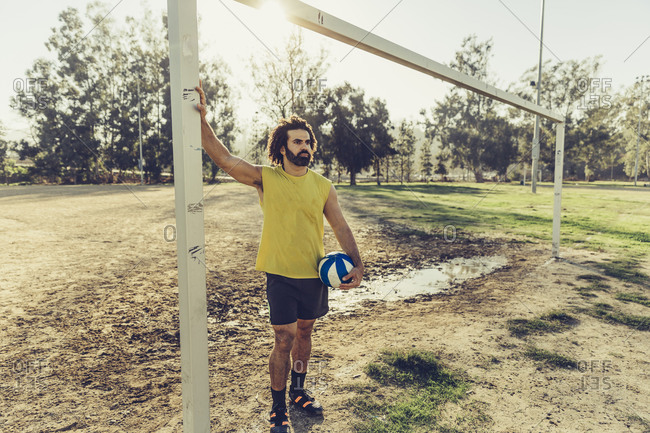 Male soccer player leaning on goal post