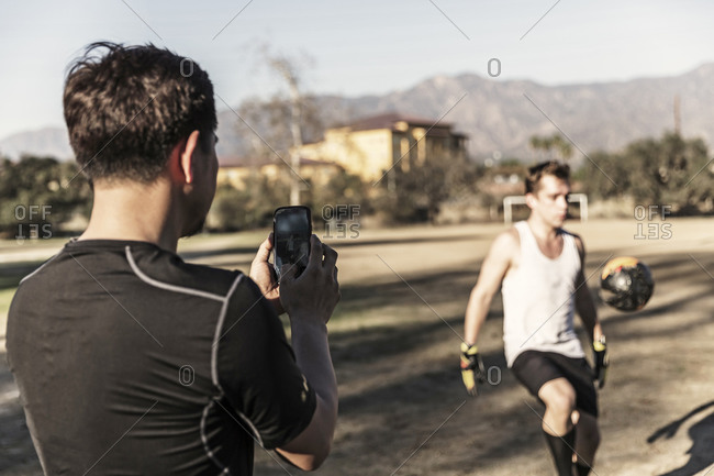 Man taking picture of athlete kicking up ball