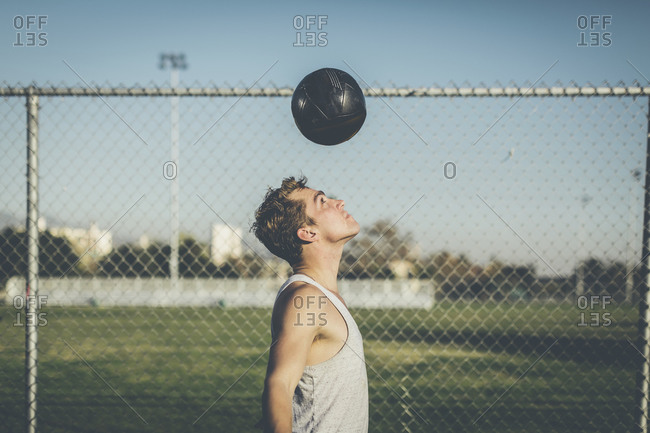 Man bouncing soccer ball off head
