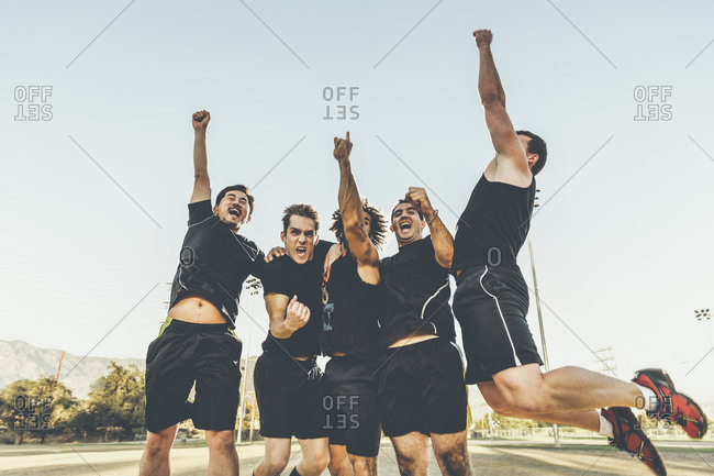 Five male soccer players jumping and cheering