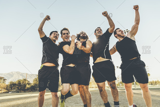 Five male soccer players cheering