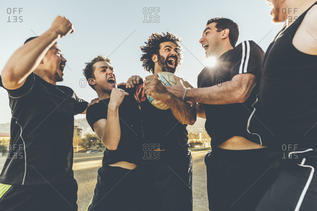 Five soccer players in celebration