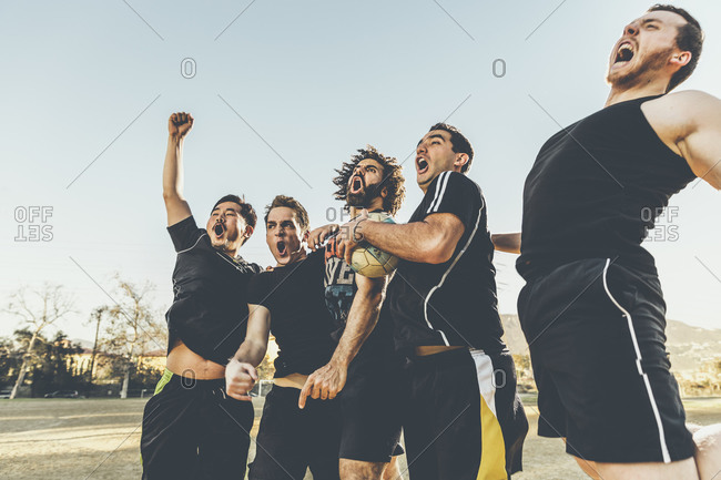 Five male soccer players in celebration