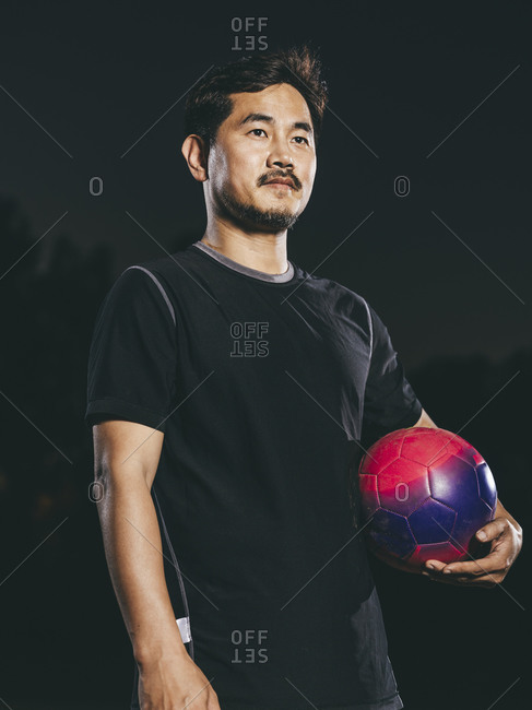 Male soccer player holding ball at night