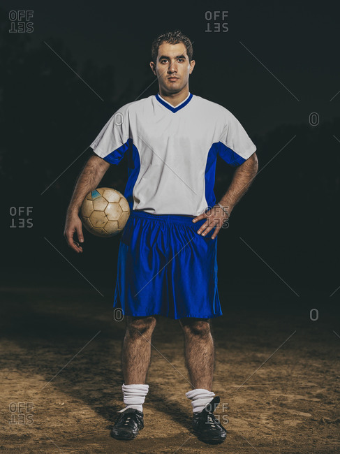 Male soccer player in soccer field at night