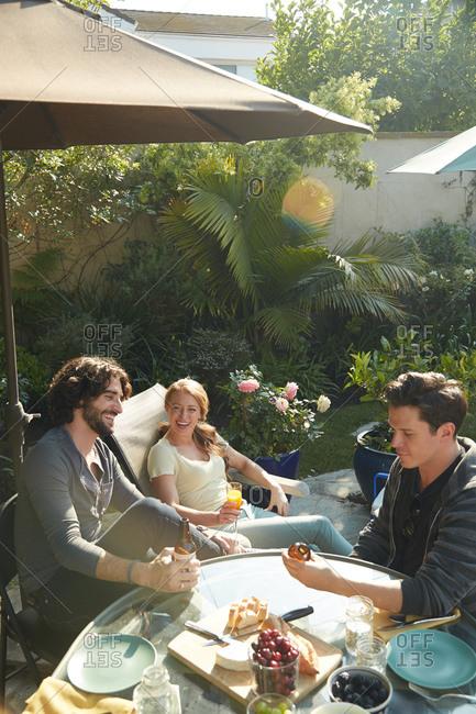 Friends laugh at a backyard picnic