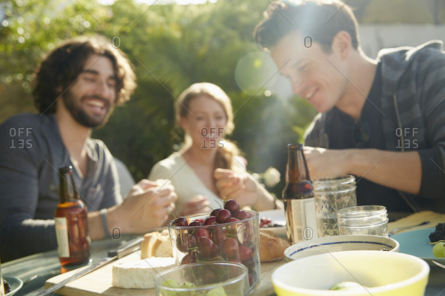 Friends laugh together at a backyard picnic
