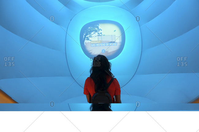 Milan, Italy - June 23, 2015: Woman reading display screen at expo in Italy
