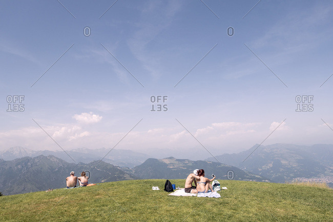 Couples relaxing on top of Monte Poieto, Italy