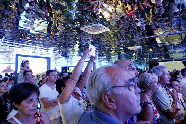 Milan, Italy - June 28, 2015: Crowd listening in mirrored room at expo in Italy