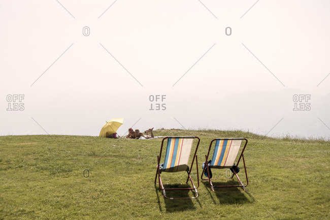 Monte Poieto, Italy - July 5, 2015: Couple relaxing on top of Monte Poieto, Italy
