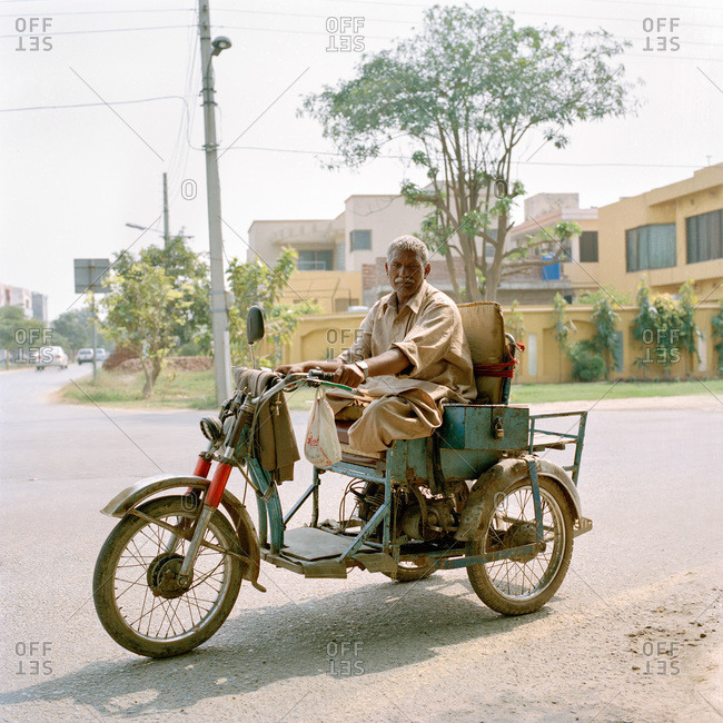 Lahore, Pakistan - March 1, 2009: Portrait of a disabled man (both of his legs are amputated) sitting in his handicap motorcycle