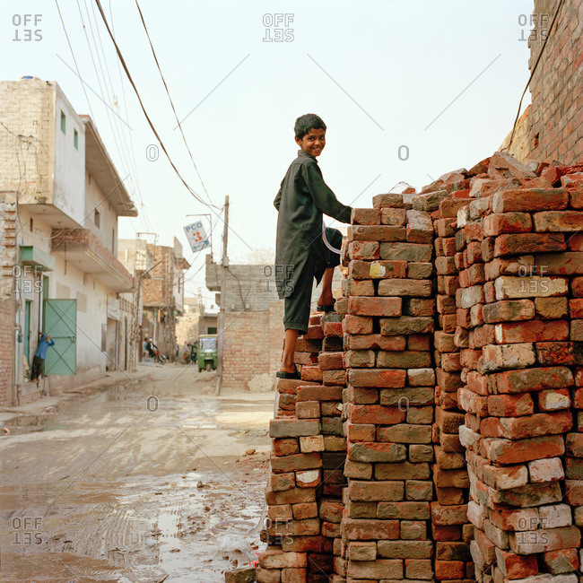 Lahore, Pakistan - March 1, 2009: Young Pakistani boy climbing a pile of bricks