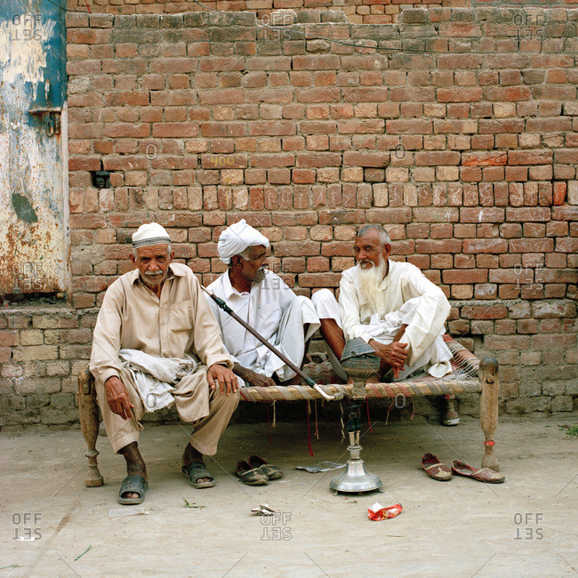 Lahore, Pakistan - March 1, 2009: Three Pakistani men sharing a hookah outside