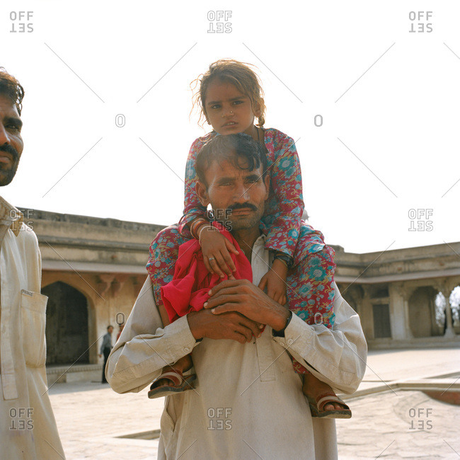 Lahore, Pakistan - March 1, 2009: Man carrying girl on his shoulders in plaza in Lahore