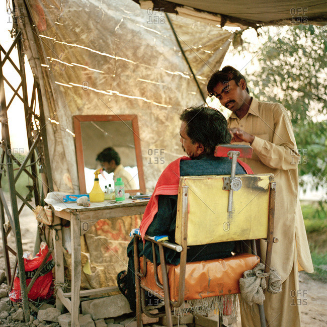 Lahore, Pakistan - March 1, 2009: Man getting haircut at rural stand in Pakistan
