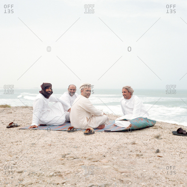 Aseela, Oman - August 5, 2011: Four men gathered on the beach in Aseela