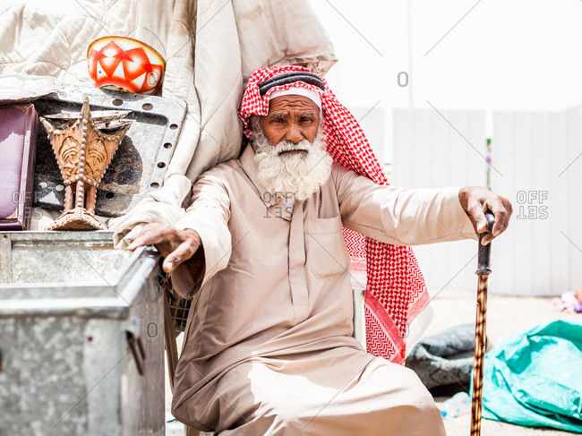 Batha, Riyadh, Saudi Arabia - June 3, 2013: Old Saudi Arabian man sitting with cane