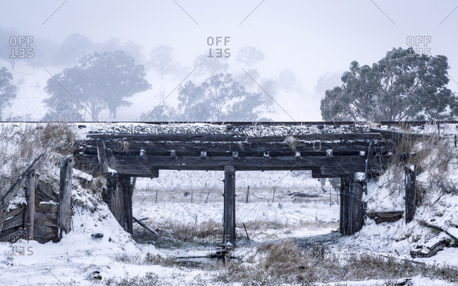 Old wooden railroad bridge above a stream in snowy landscape