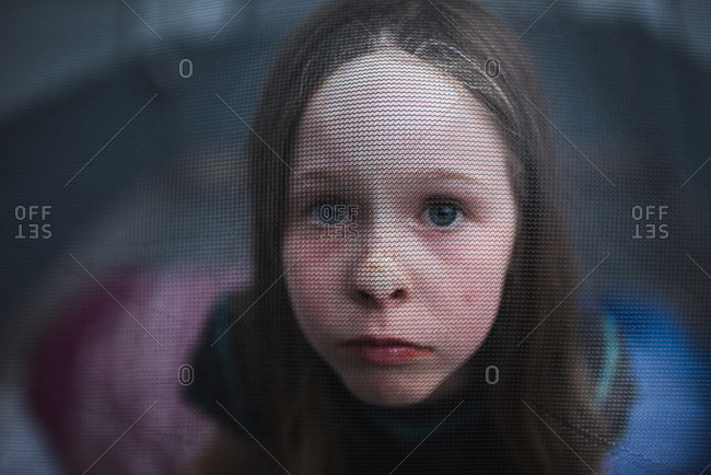 Portrait of a girl through a mesh camping tent window