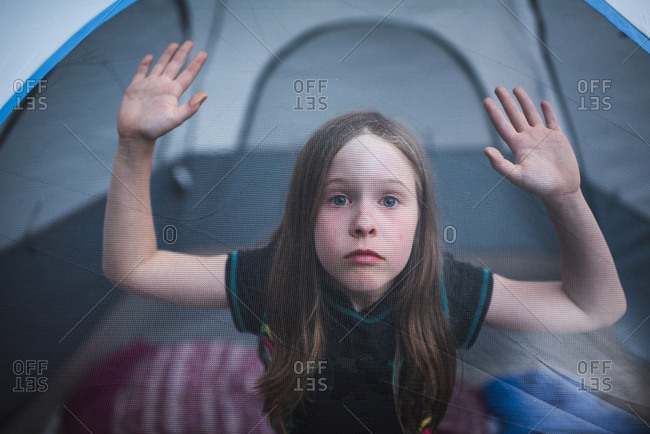 A girl looks out from a mesh camping tent window
