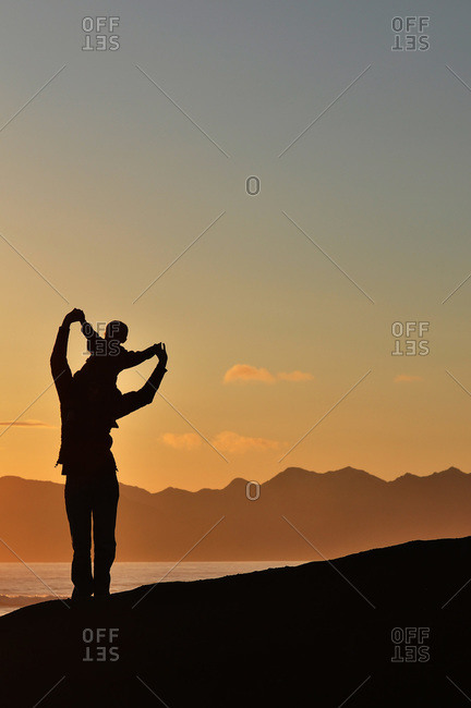Man with child on shoulders silhouetted on oceanfront hill at sunset
