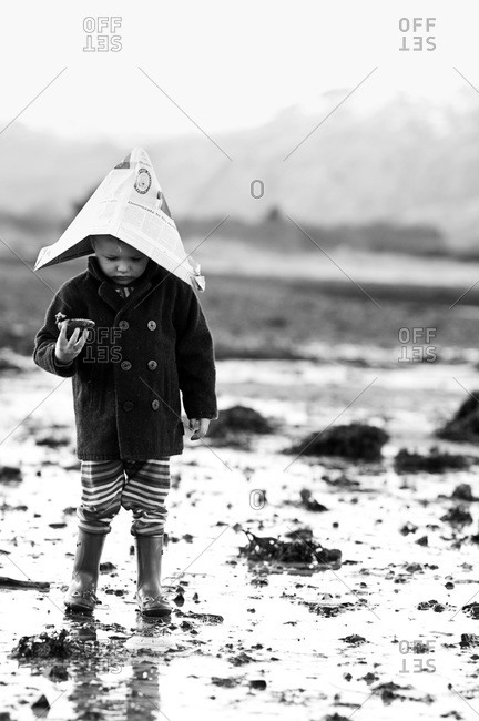 Young child wearing boots and a newspaper hat collects shells on the beach