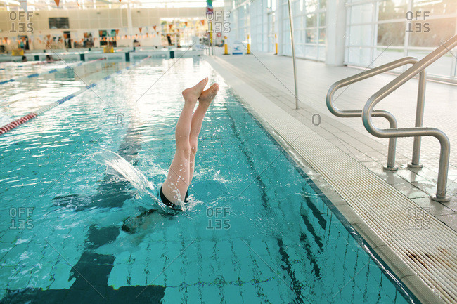 A girl dives into a swimming pool