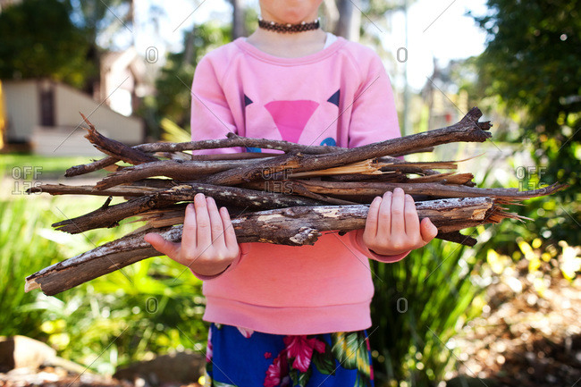 A girl holds a armful of kindling branches