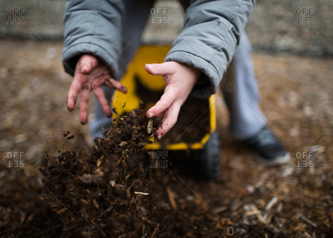 A young boy empties dirt from a toy truck