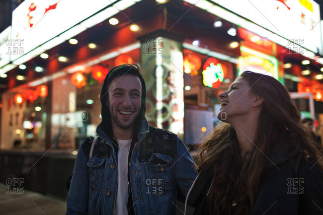Laughing young couple on street corner in front of Chinese restaurant at night