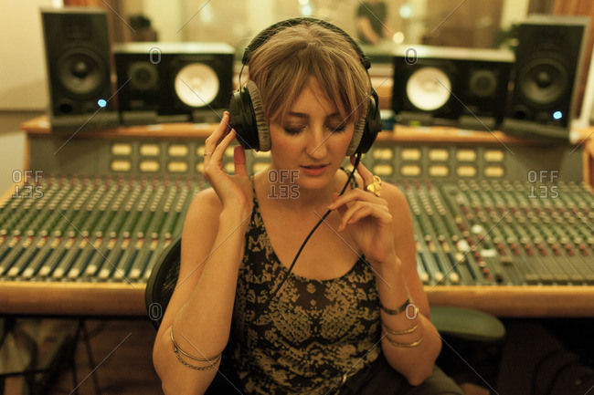 Portrait of a young woman wearing headphones at sound board in recording studio