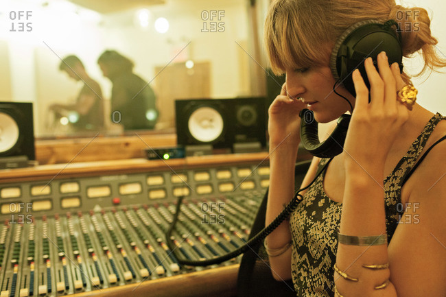 Young woman listening to a recording in a music studio