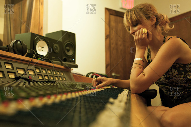 Portrait of a young woman seated at mixing board in recording studio