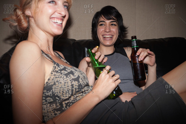 Young women sitting on couch drinking beer at party