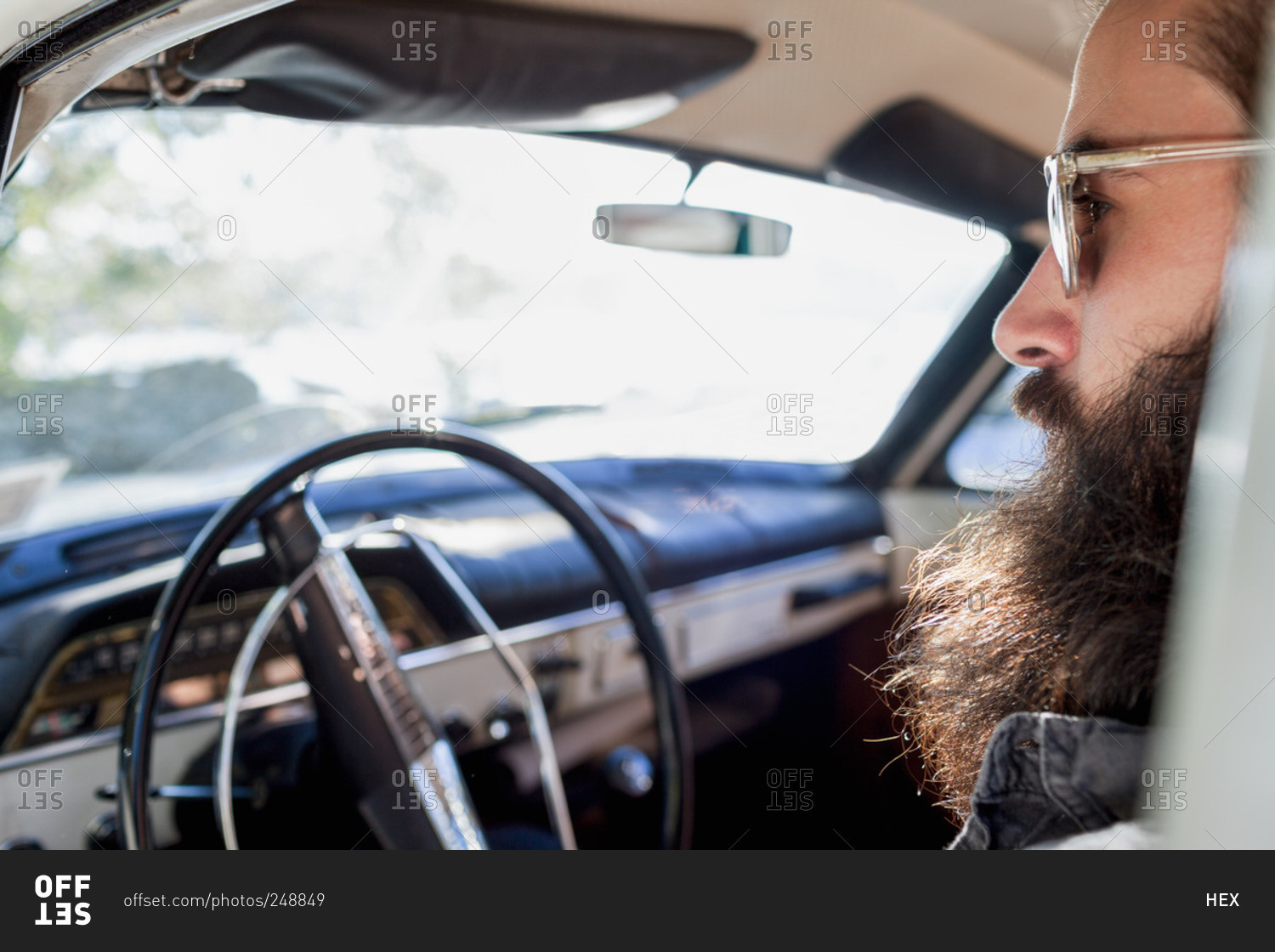 View Through Side Window Of Bearded Man In Front Seat Of Car Stock