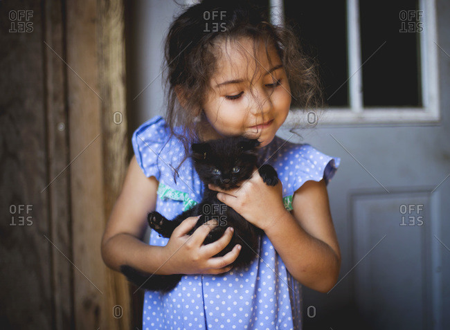 Young girl holds a fuzzy black kitten