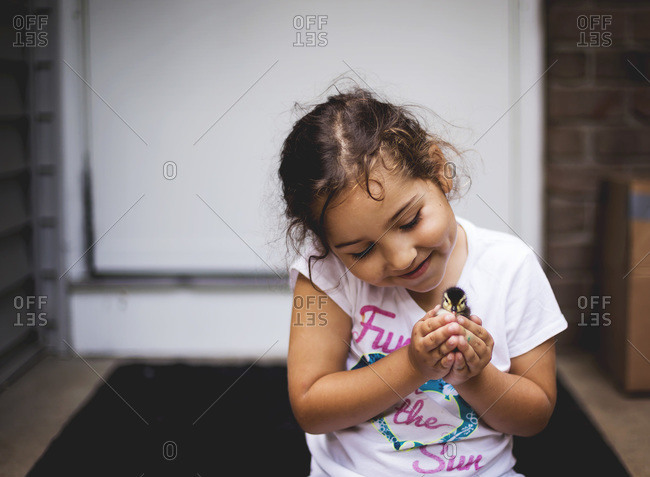 Girl adoringly holds a baby duckling in her cupped palms