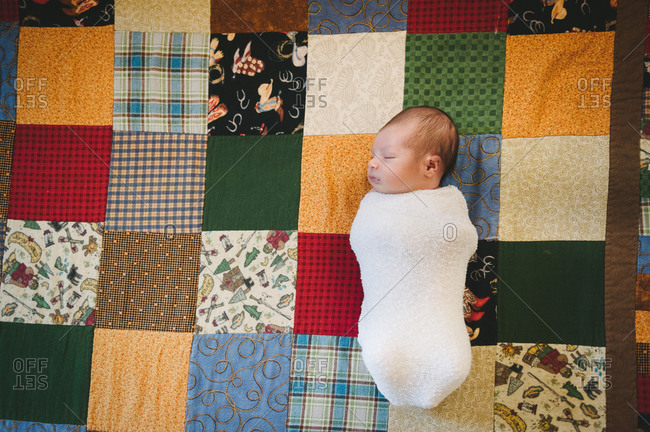 Swaddled baby on a patchwork quilt