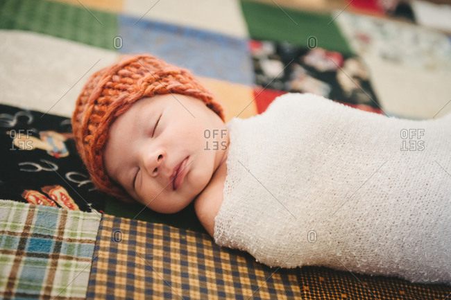 Baby in a knit cap on a patchwork quilt