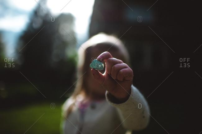 Little girl holding up a blue eggshell
