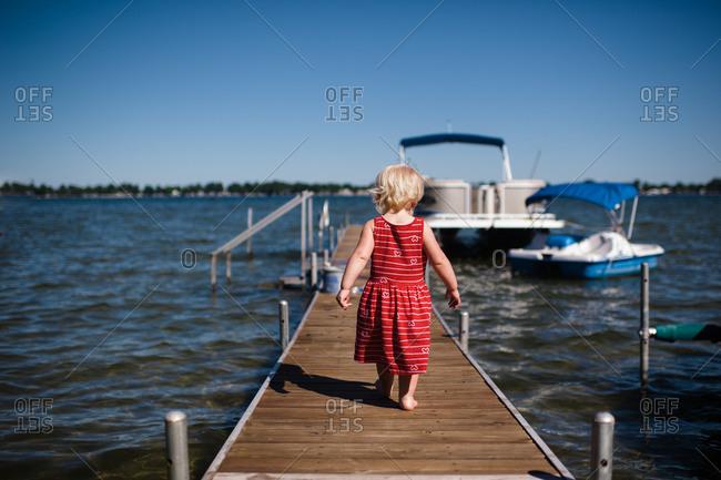 Little girl walking on a dock