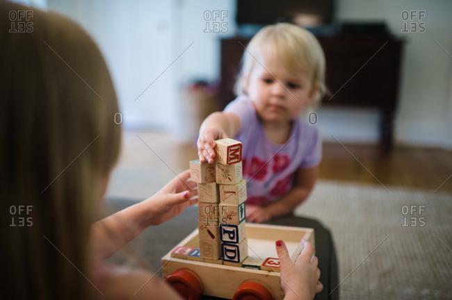 Little girls stacking wooden blocks