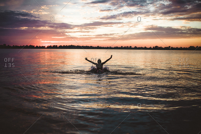 Girl in a lake at sunset